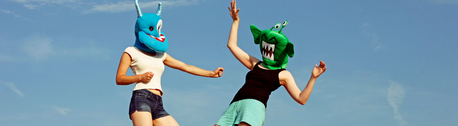 Zwei Menschen mit lustigen Monster-Masken kämpfen.