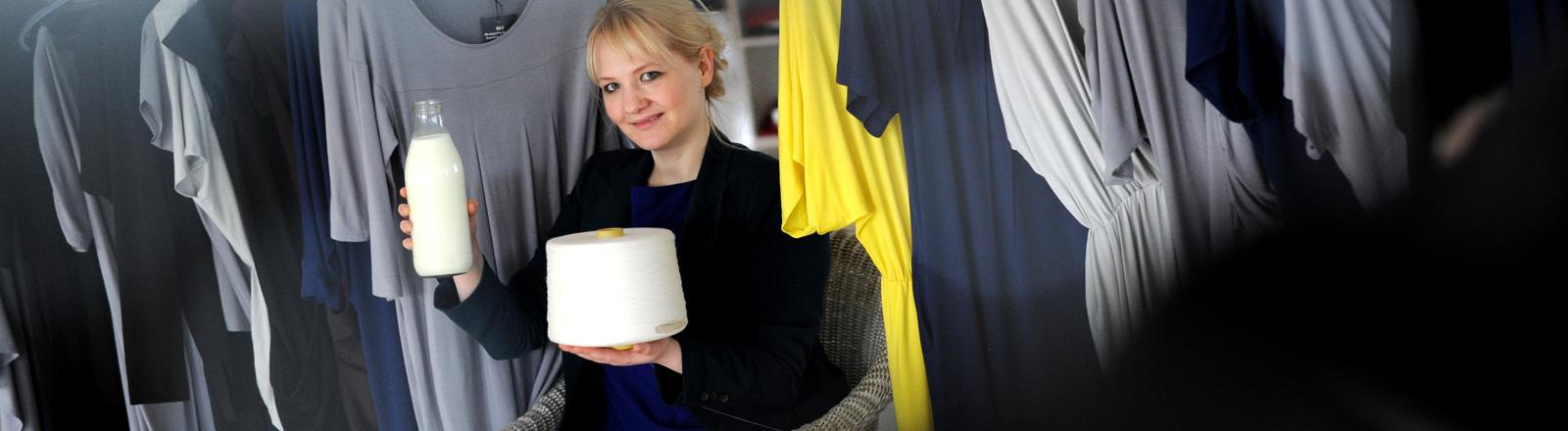 Die Modedesignerin und Biochemikerin Anke Domaske posiert am 19.09.2011 in Hannover mit einer Milchflasche, aus Milchfasern versponnenes Garn und daraus hergestellten Kleid.