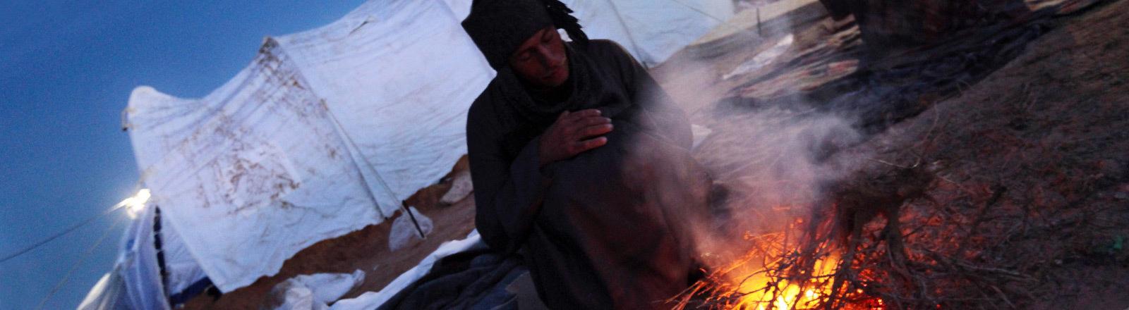 Ein Mann an einem Lagerfeuer in einem Flüchtlingscamp.