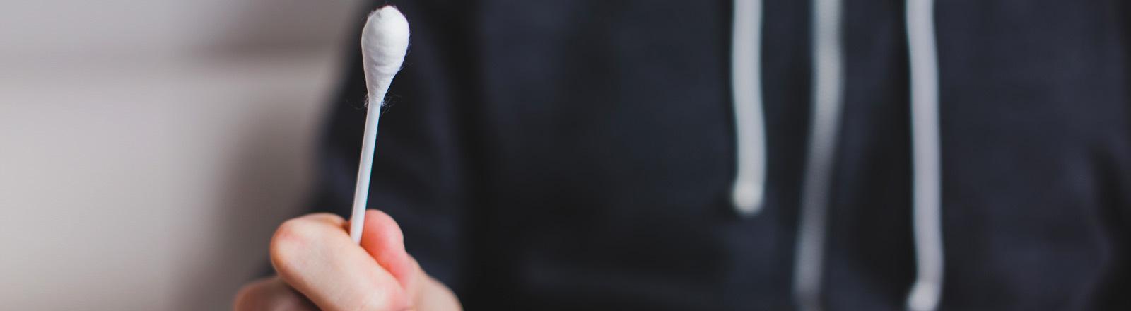 Ein Mann hält ein großes Wattestäbchen in der Hand.