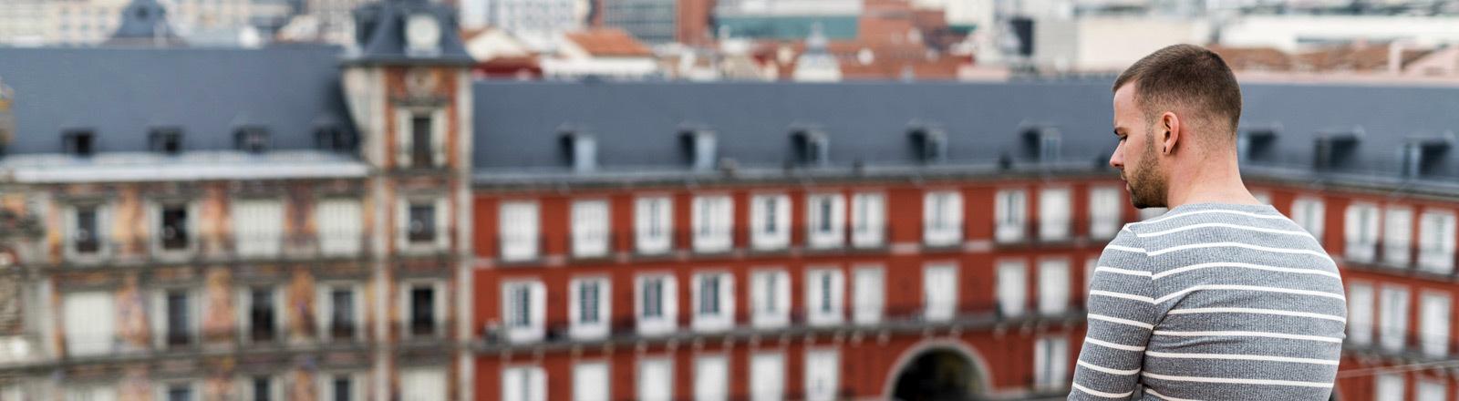 Ein Mann sitzt auf einem Dach in der Stadt.