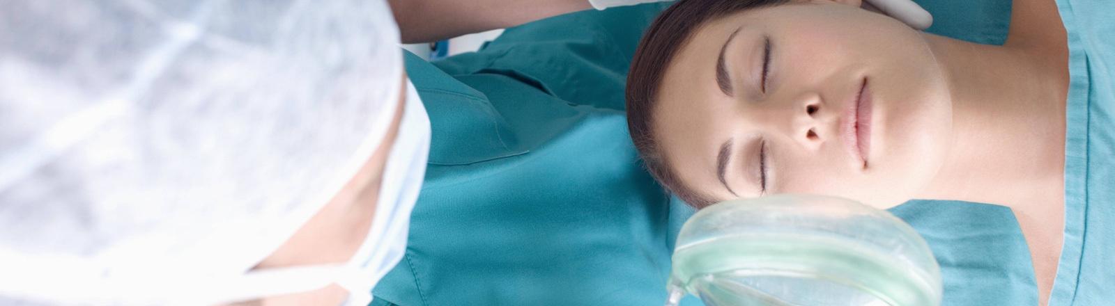Ein Anästhesist betäubt Patientin.