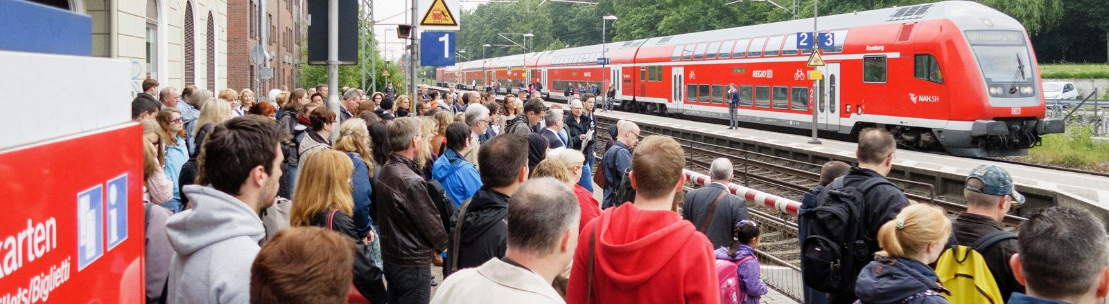 Pendler warten an einem Bahnsteig auf einen Regionalzug.