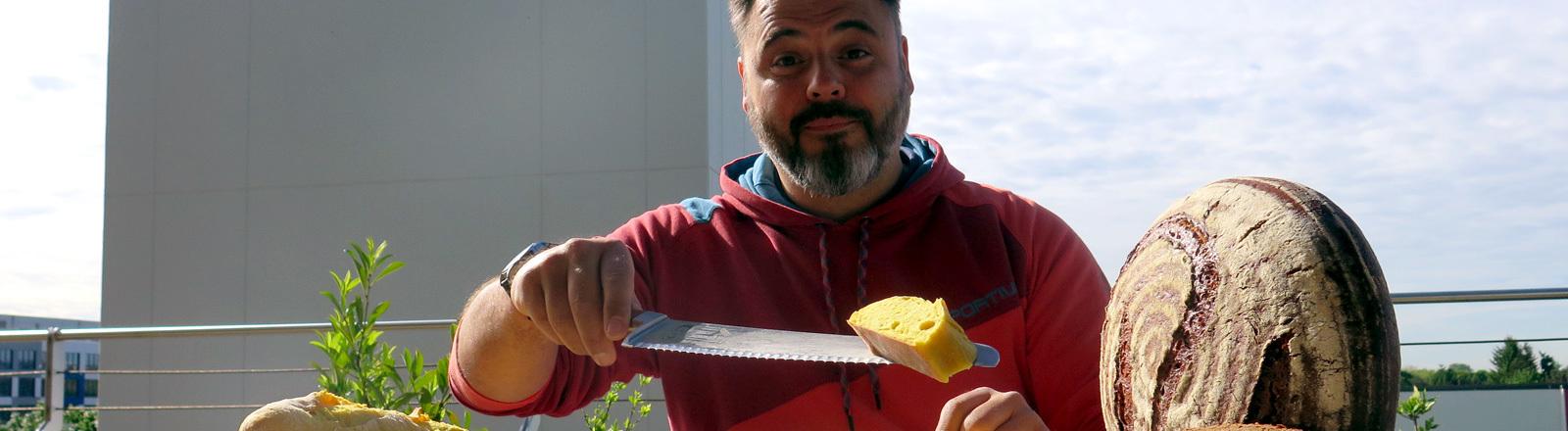 Brotsommelier Ralf Gießelmann bietet ein Stück vom Mango-Curry Baguette an.