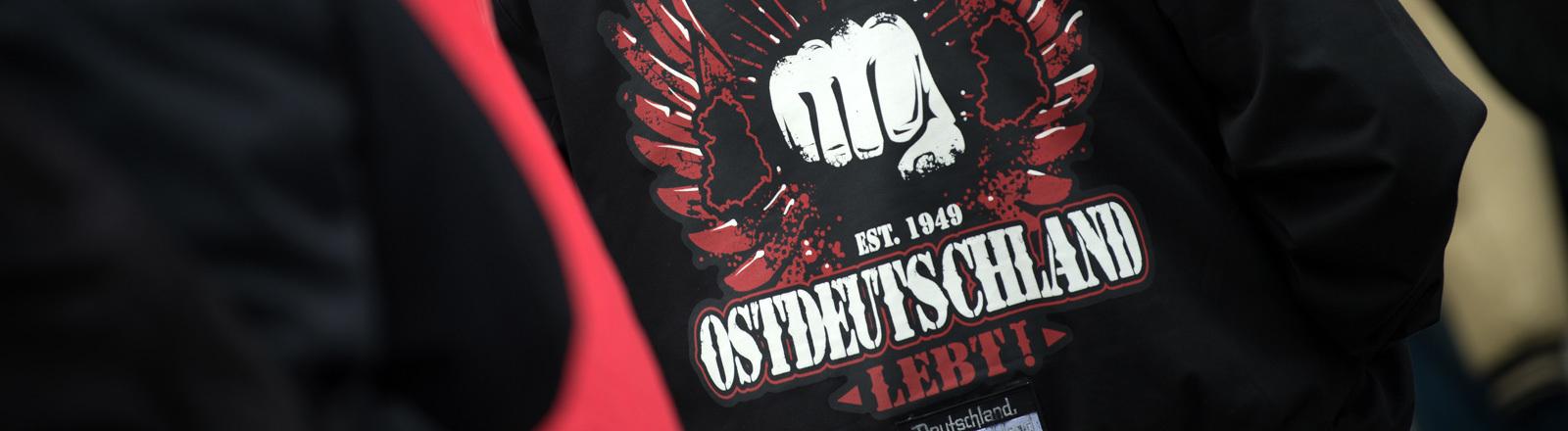Ein Teilnehmer einer Pro-Le-Pen Demonstration der Thügida vor der Frauenkirche in Dresden (Sachsen) trägt am 06.05.2017 eine Jacke mit den Aufdrucken «Deutschland mein Vaterland, Est. 1949 Ostdeutschland lebt und Deutschland über alles».