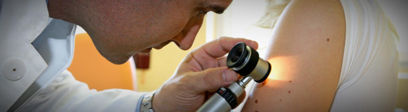 Ein Hautarzt untersucht die Haut einer Patientin.