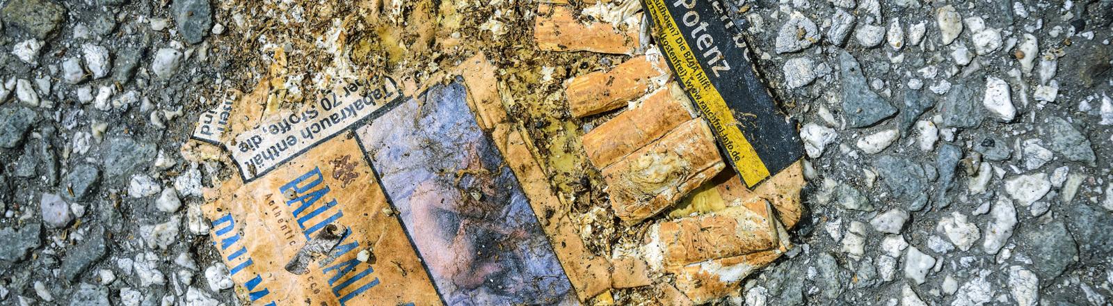 Eine aufgeweichte, zertretene Zigarettenschachtel auf der Straße