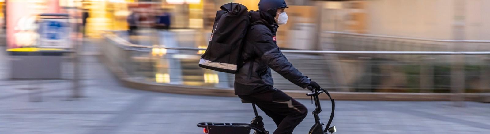 Ein Fahrradkurier des Anbieters Gorillas ist auf einem Fahrrad untwegs.