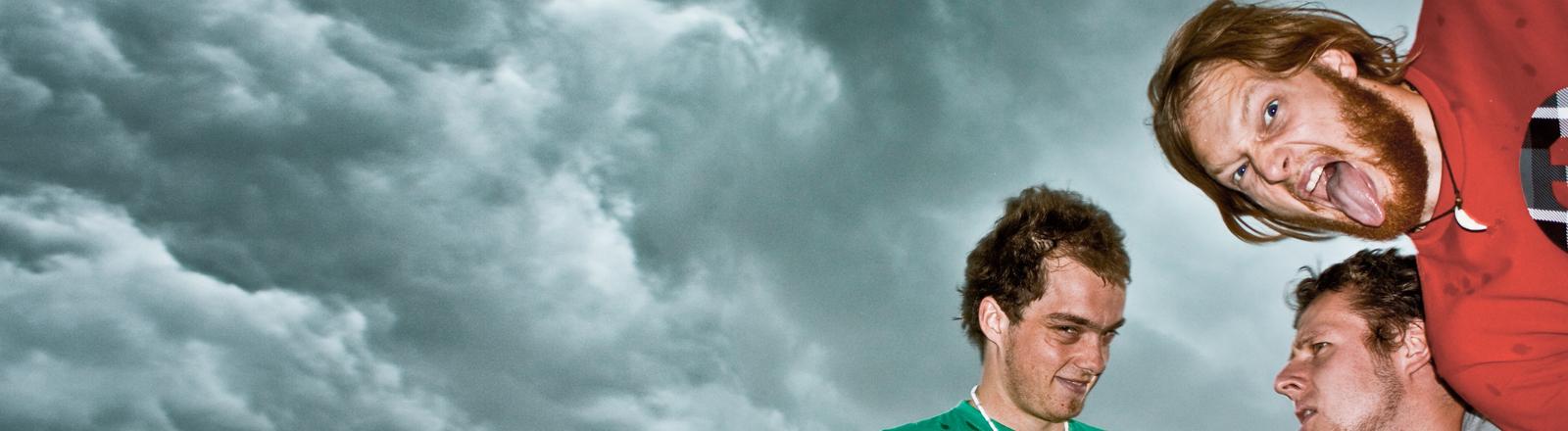 Drei Männer gucken lustig, betrunken, aggressiv, dumm in die Kamera. Im Hintergrund Wolken.
