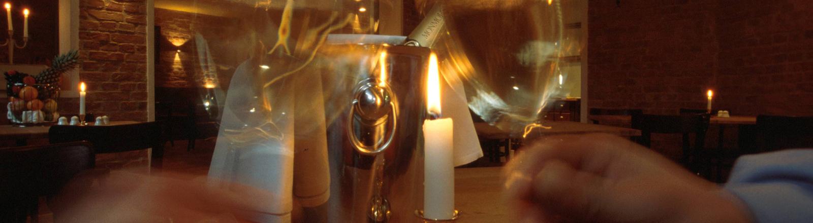Ein Paar in einem Restaurant bei Kerzenlicht. Romantik. Stoßen an. Sie haben was zu feiern.