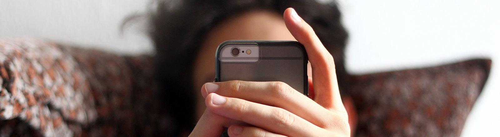 Jugendlicher vor dem Smartphone.