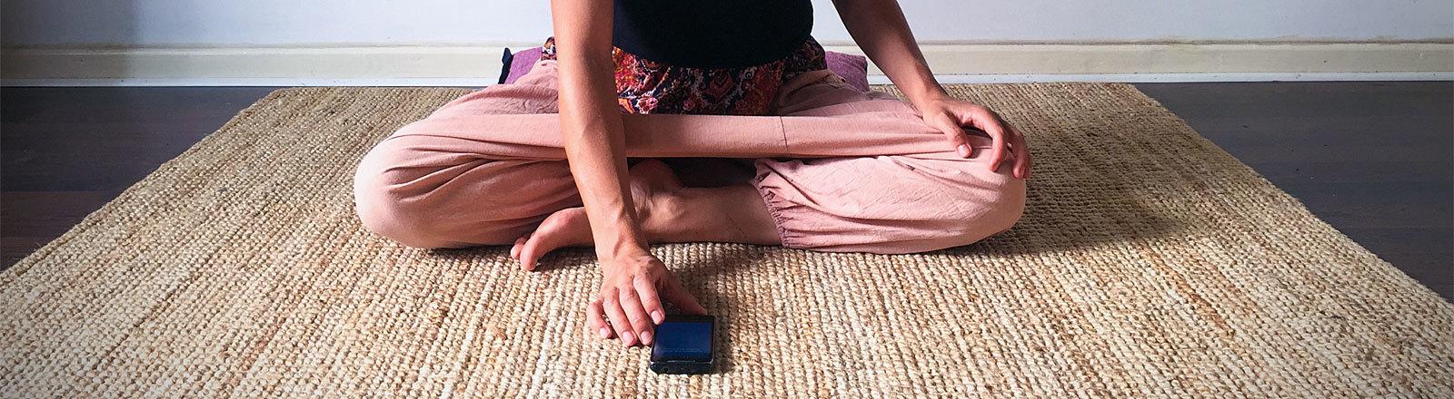 Frau tippt auf Smartphone im Schneidersitz