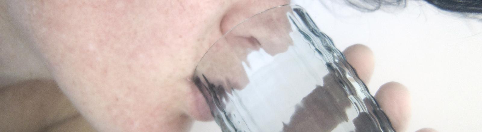 Eine Frau trinkt Wasser aus einem Glas