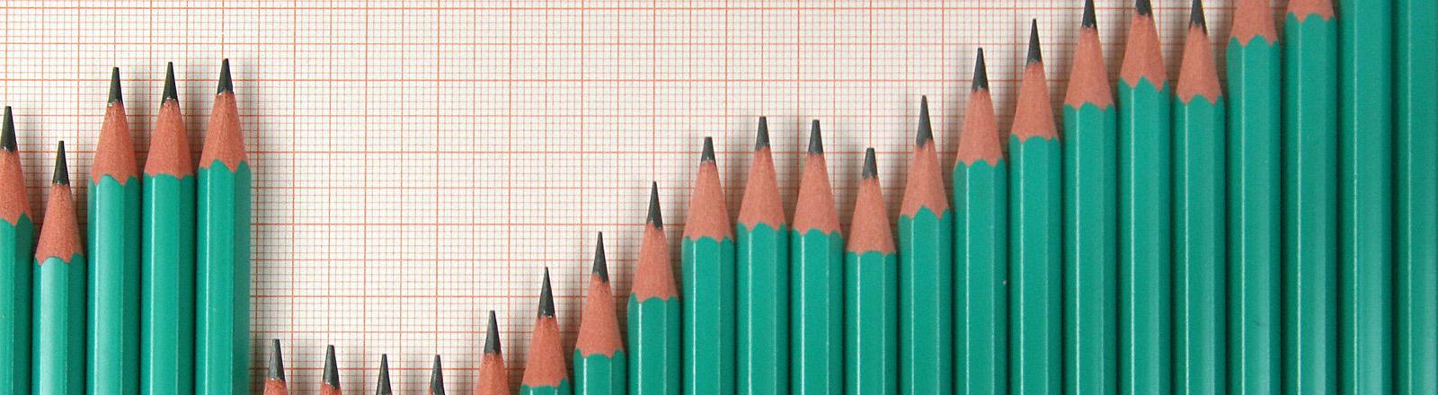 Symbolbild: Bleistifte formen einen Börsenkurs.