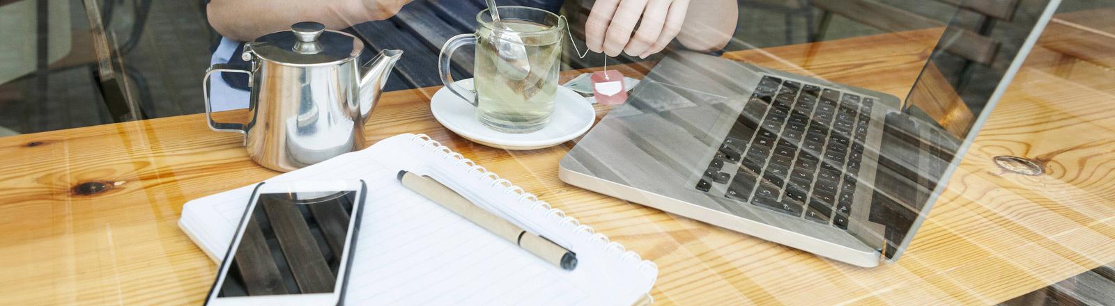 Eine Frau sitzt mit Smartphone und Laptop im Café.