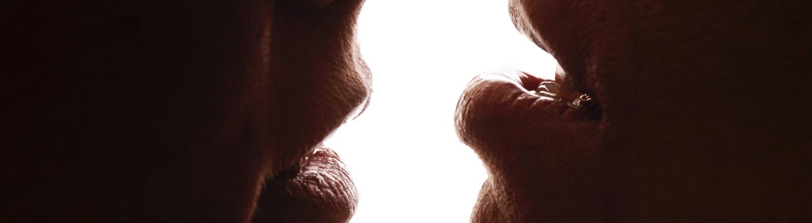 Ein Mann und eine Frau sind kurz davor sich zu küssen.