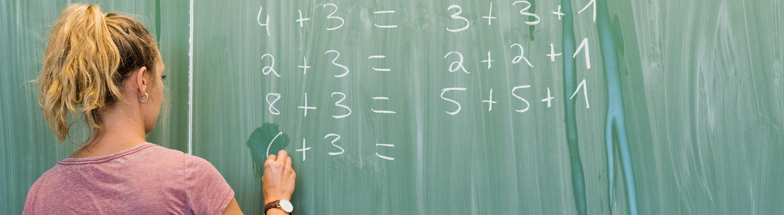 Eine Lehrerin schreibt mit Kreide an eine Tafel.