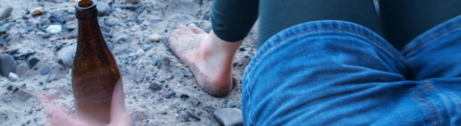Frau greift am Strand auf dem Rücken liegend zu einer Bierflasche.