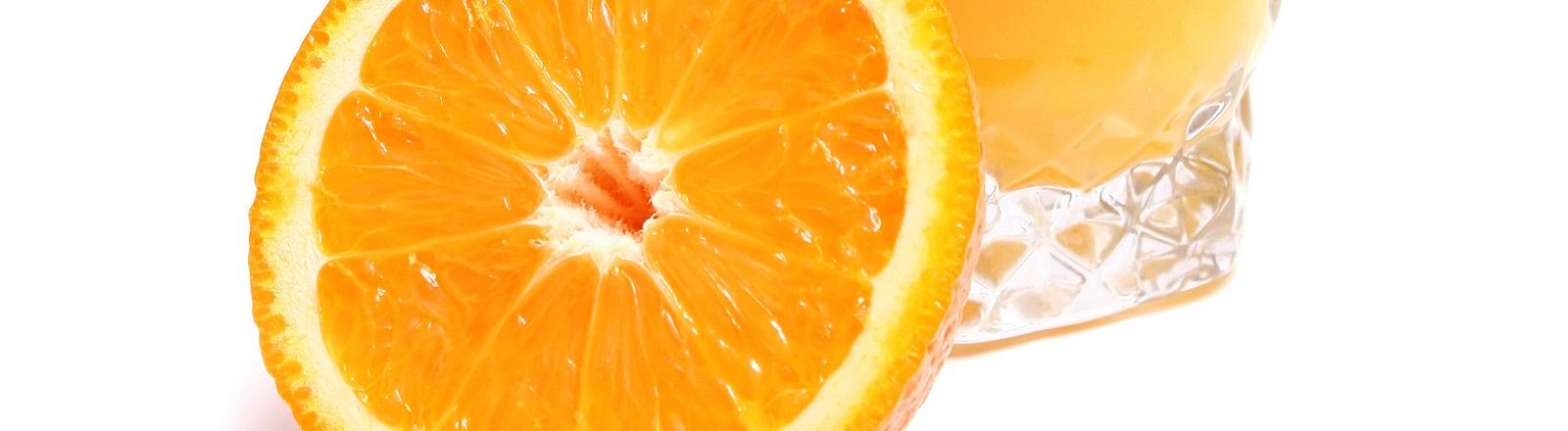 Ein Glas Orangensaft, daneben eine halbierte Orange.