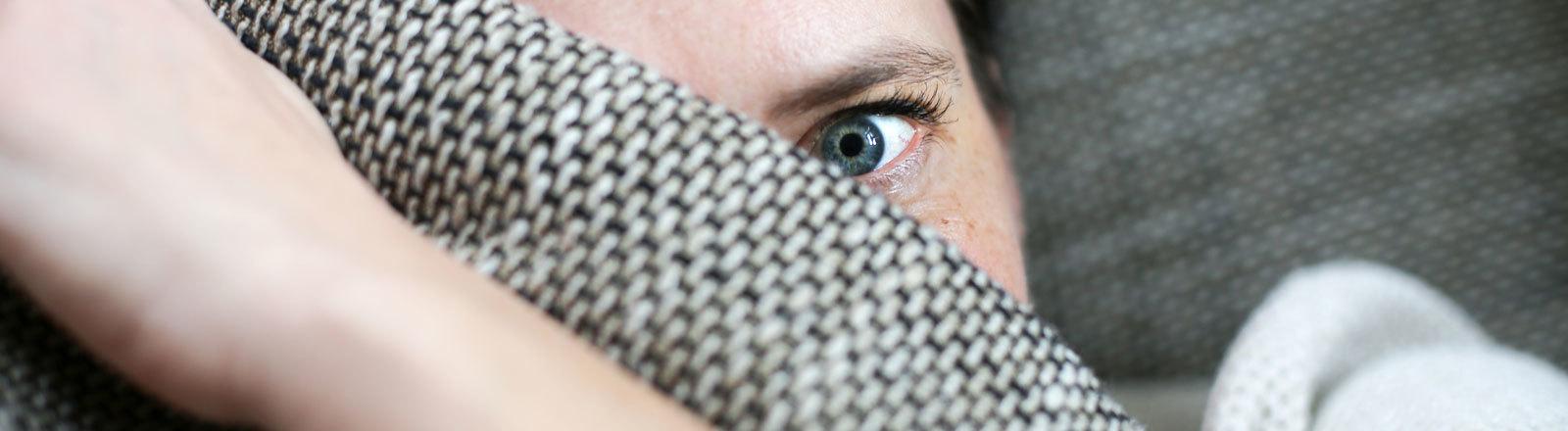 Frau versteckt sich hinter einer Decke.