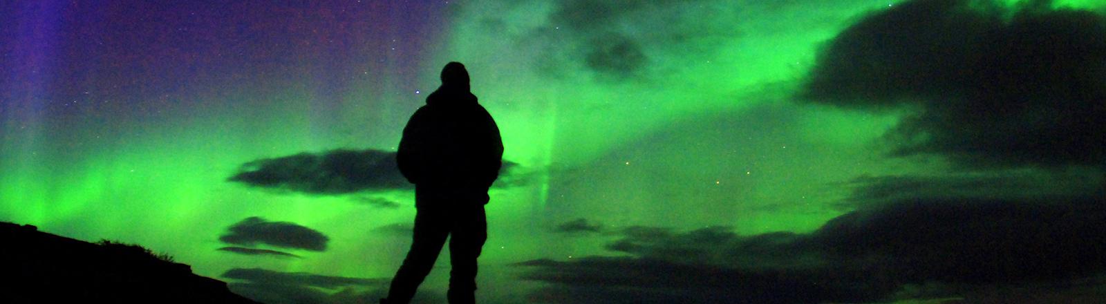 Am Porsangerfjord in der Finnmark in Nordnorwegen, rund 60 Kilometer südlich des Nordkaps nahe des Ortes Repvag, beobachtet in der Nacht am 14.09.2005 ein Mann das farbenprächtige Schauspiel eines Polarlichts das durch Wolkenlücken scheint