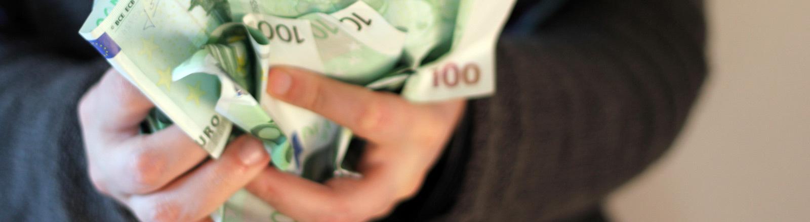 Eine Person hält viele 100-Euro-Scheine in beiden Händen.