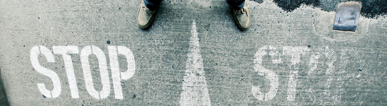 Ein Mann steht vor einer Pfeilmarkierung, die auf dem Boden neben dem Wort Stop zu sehen ist.