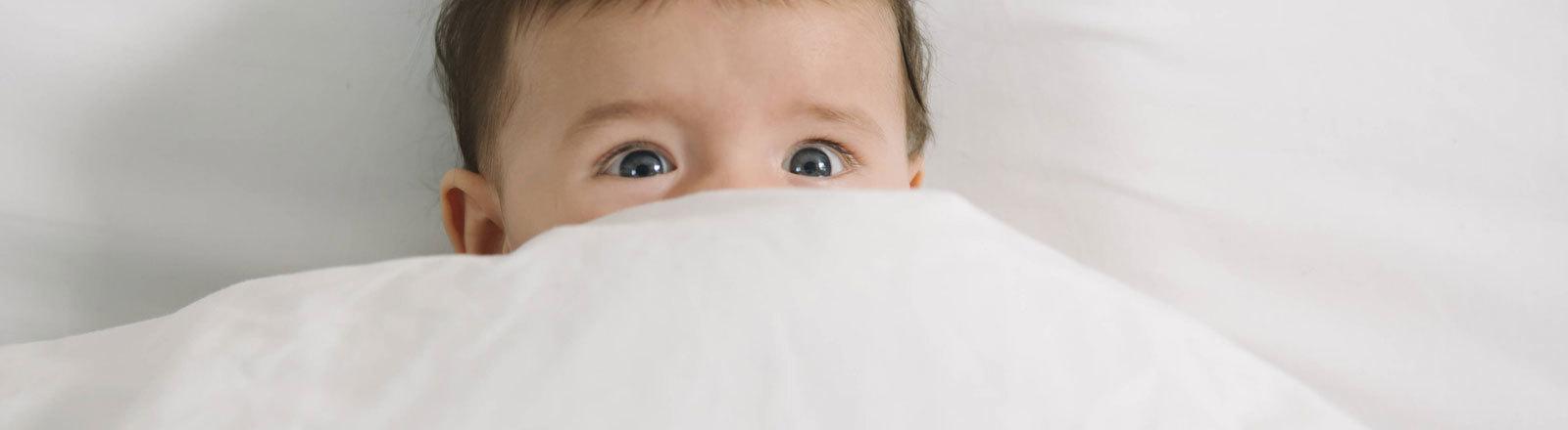 Baby blickt ängstlich unter der Bettdecke vor.