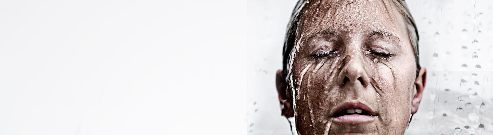 Über das Gesicht einer Frau läuft Wasser.