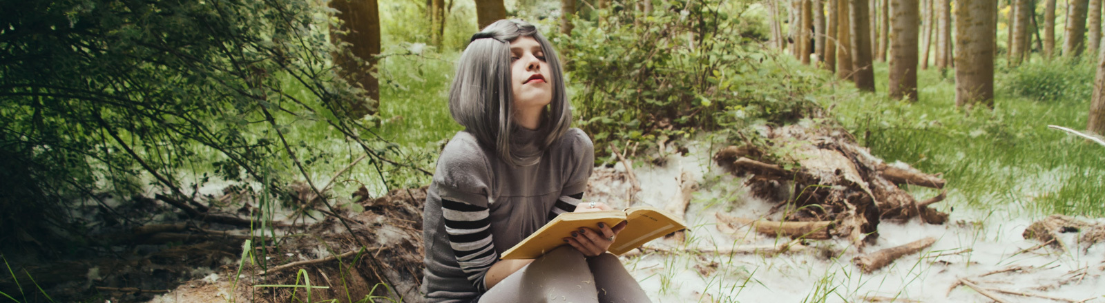Eine junge Frau im Wald liest ein Buch.