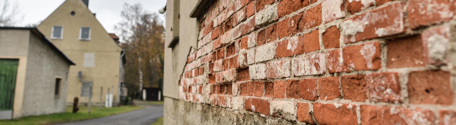 Eine Häuserwand, an der der Putz abgebröckelt ist.