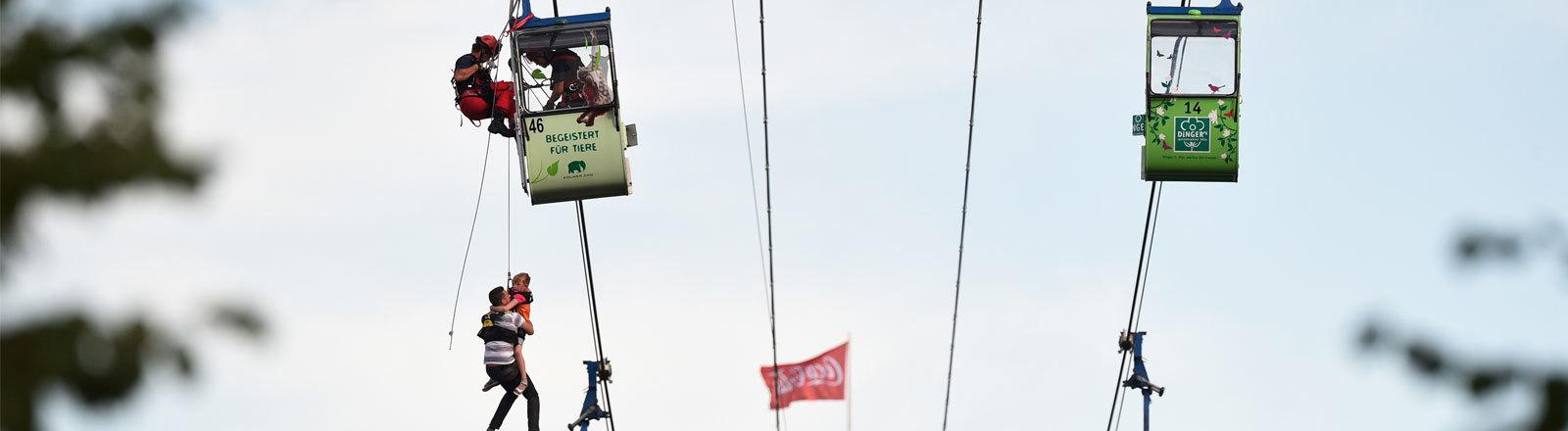 Höhenretter der Feuerwehr befreien am 30.07.2017 in Köln (Nordrhein-Westfalen) Fahrgäste aus den Gondeln.