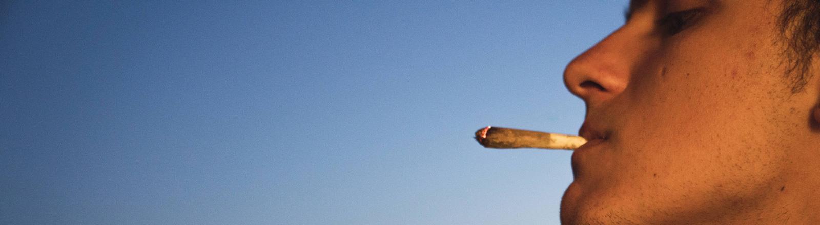 Ein junger Mann zieht an einem Joint.