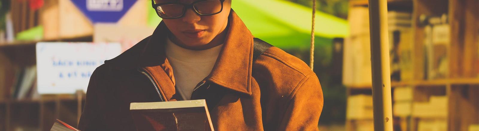 Ein junger Mann schaut auf ein Buch.