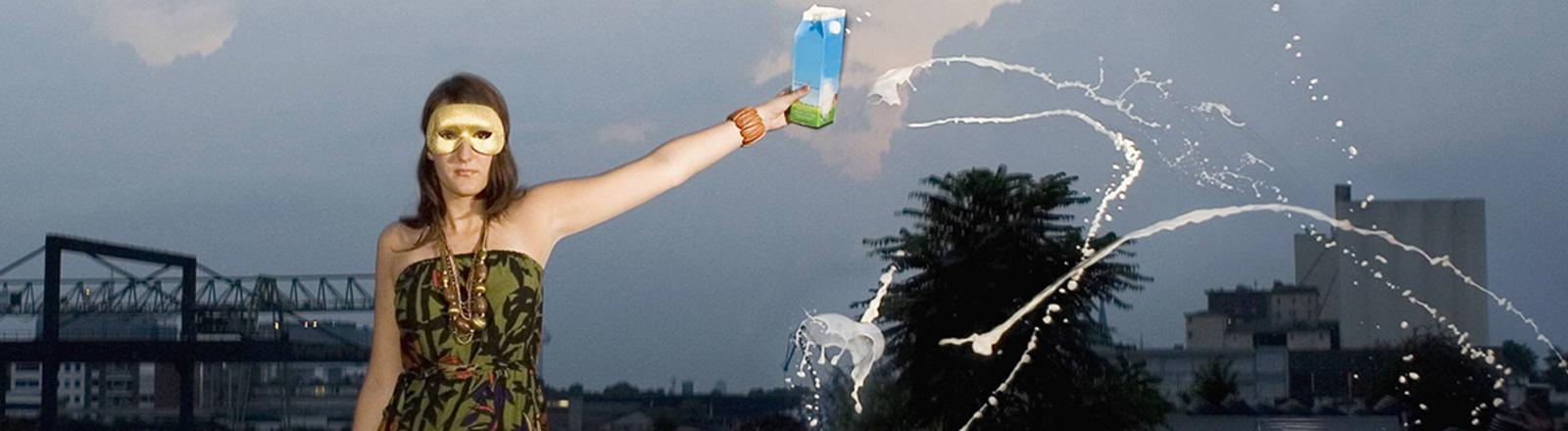 Eine Frau mit Maske verschüttet auf einem Industriegelände Milch.