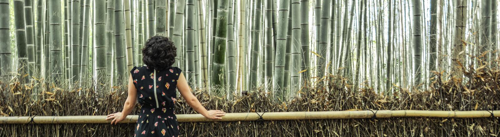 Eine Frau steht mit dem Rücken zu uns vor einer Bambuswand.