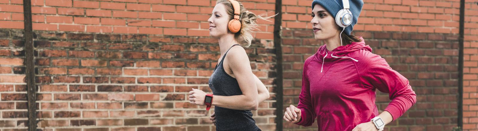 Zwei Mädels joggen mit Fitnessarmband und Kopfhörern.