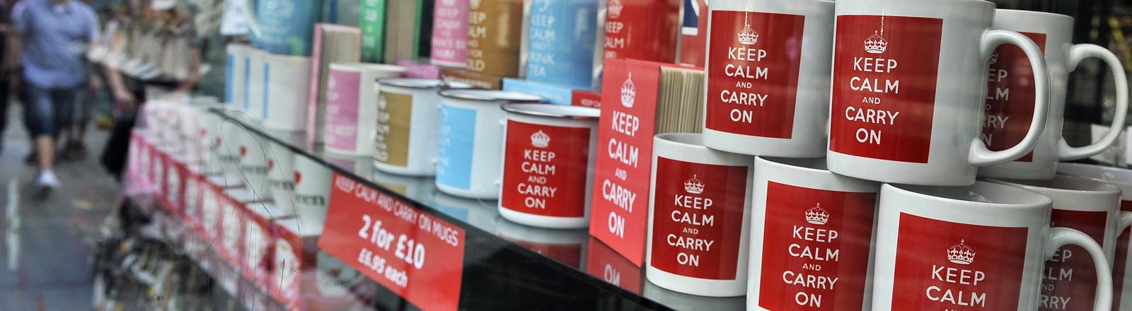 """Ein Souvenirshop in dessen Schaufenster Tassen zu sehen sind, auf denen """"Keep calm and carry on"""" steht."""
