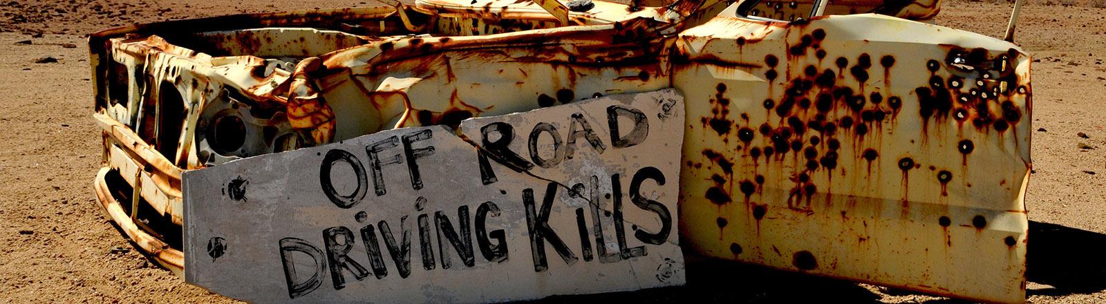 """Ein Autowrack mit einem Schild davor: """"Off road driving kills"""""""