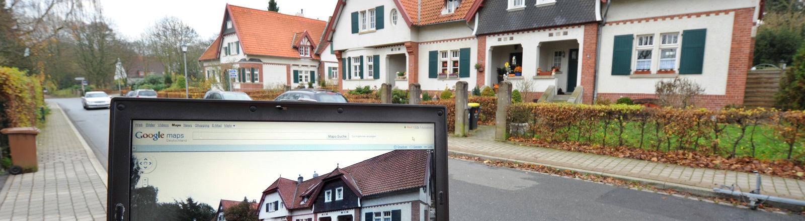 Ein Google-Streetview-Foto eines Hauses auf einem Laptop im Hintergrund das Haus selbst.