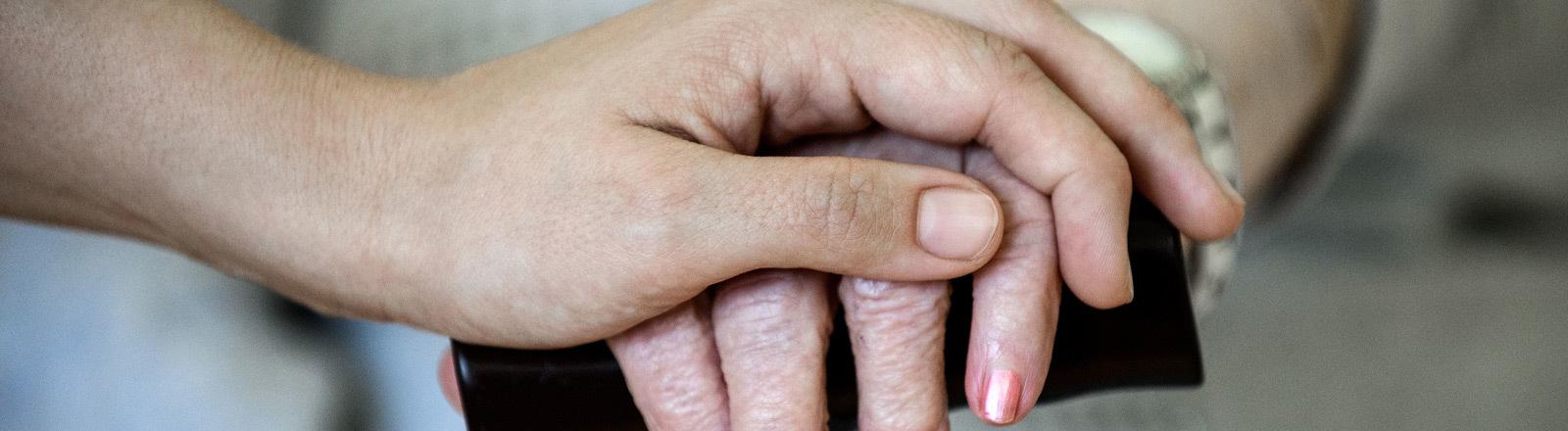 Eine Pflegerin hält die Hand einer Patientin.