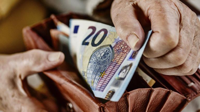 Ein Mann hält ein Portemonnaie und einen 20-Euro-Schein in der Hand.