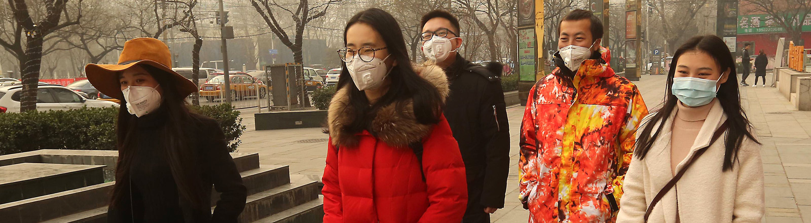 Junge Chinesen gehen eine Straße lang und tragen dabei Atemmasken.