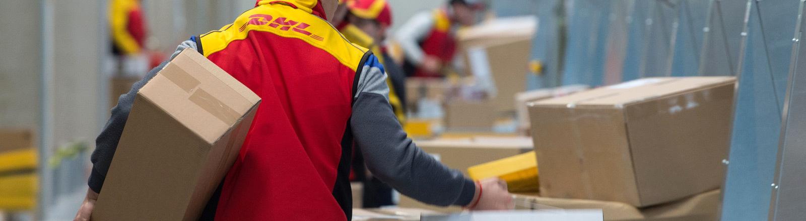 Ein DHL-Mitarbeiter sortiert Pakete.