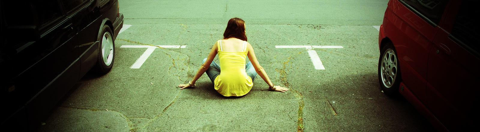 Frau sitzt auf freiem Parkplatz.