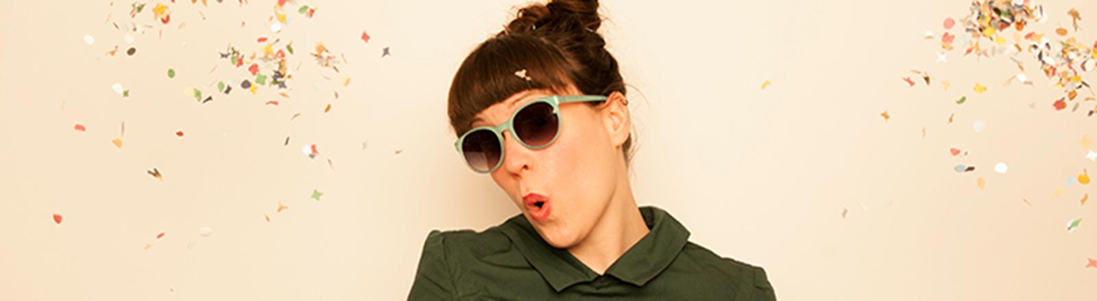 Eine junge Frau mit Sonnenbrille wirft Konfetti in die Luft und freut sich.