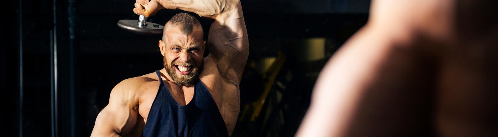 Ein Bodybuilder mit dicken Armen steht vor dem Spiegel und schaut sich dabei zu, wie er Gewichte hebt.