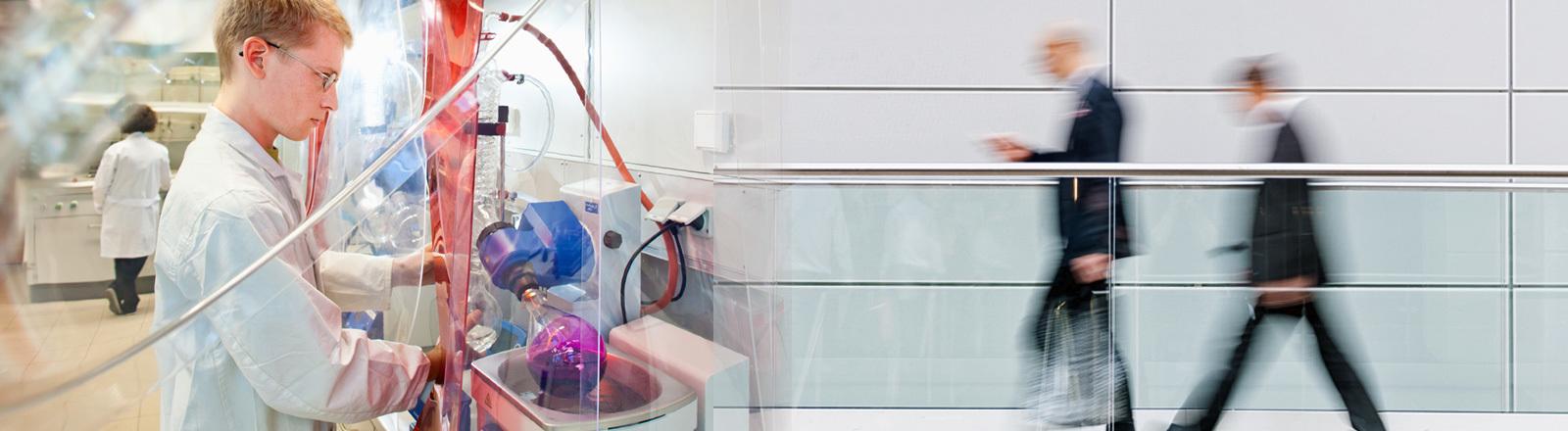 Junger Forscher in einem Labor an der Uni Chemnitz und unscharfe Anzugträger.