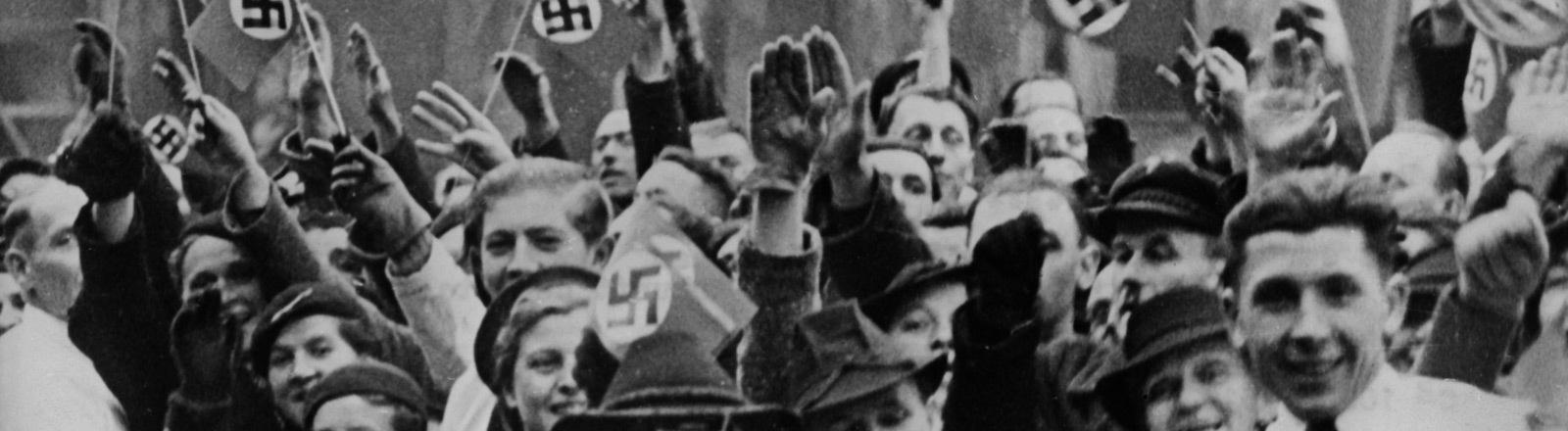 Menschen freuen sich bei der Ankunft von Rudolf Hess. Manche zeigen den Hitlergruß, andere schwenken Hakenkreuz-Flaggen.