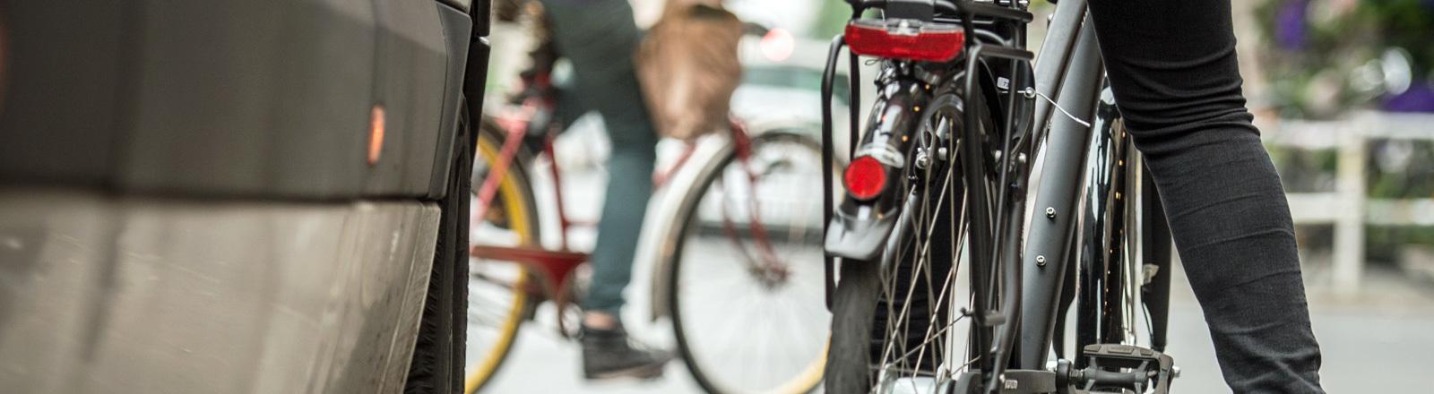 Die vordere rechte Seite eines Autos. Sehr nahe, rechts daneben steht ein Fahrradfahrer. Im Hintergrund fährt ein Fahrrad.